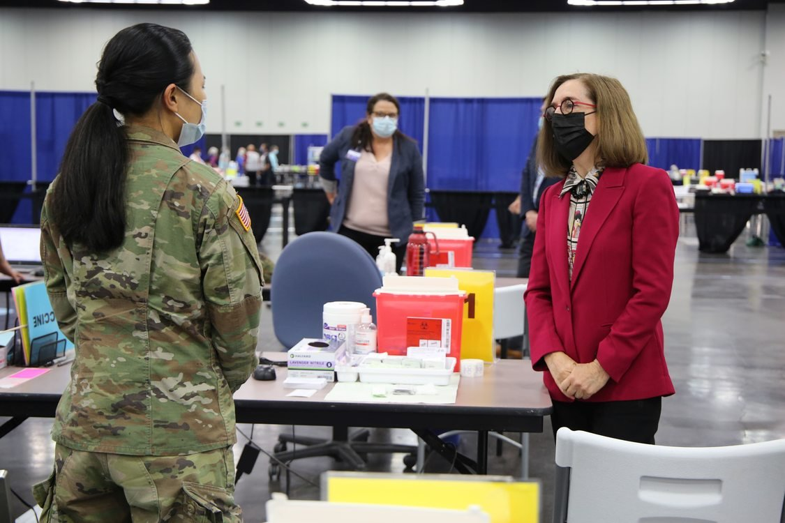 Governor Kate Brown and another woman from the National Guard wear masks at the Oregon Convention Center mass COVID-19 vaccination site