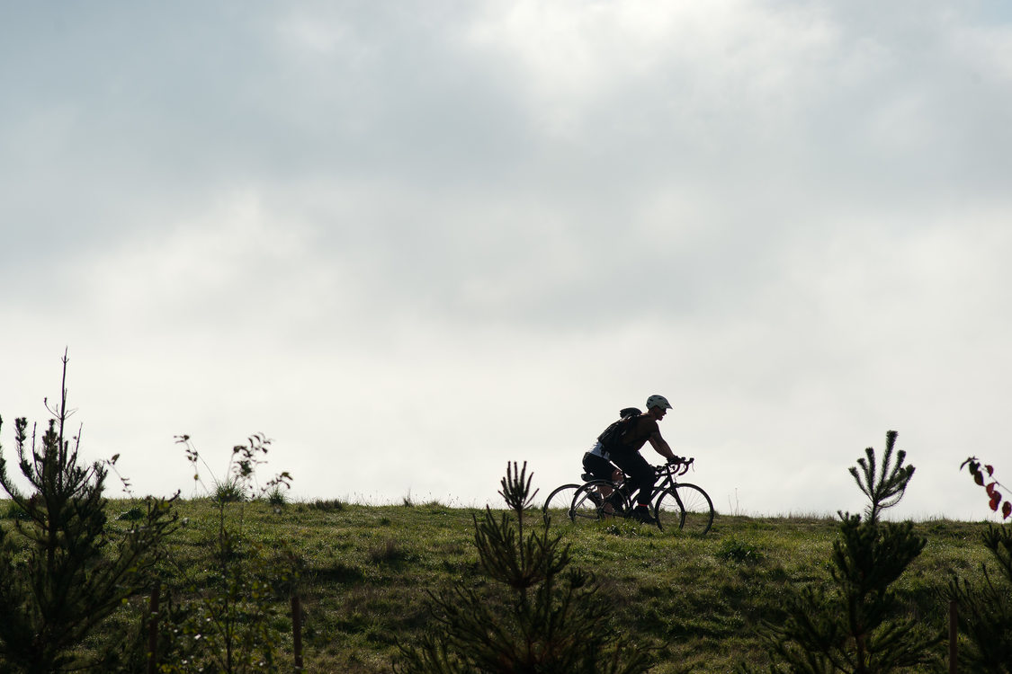 Two cyclists ride their bikes side by side along the Marine Drive trail in northeast Portland