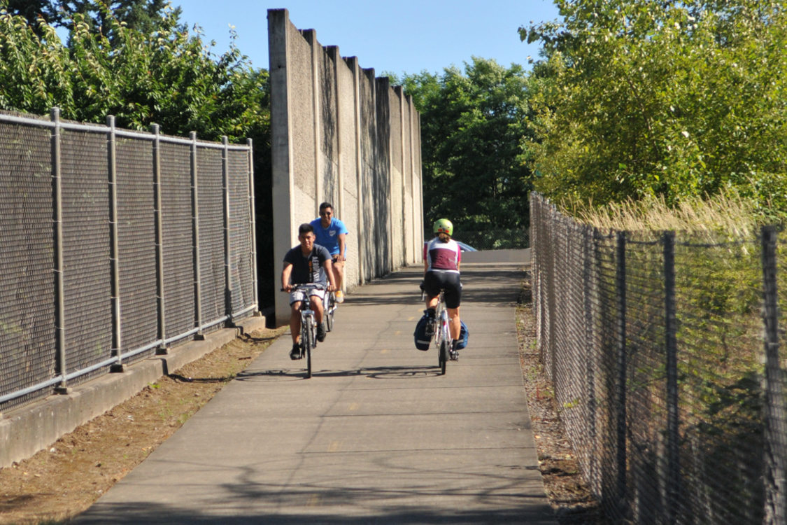 Cyclists ride their bikes along a dedicated paved trail in Portland