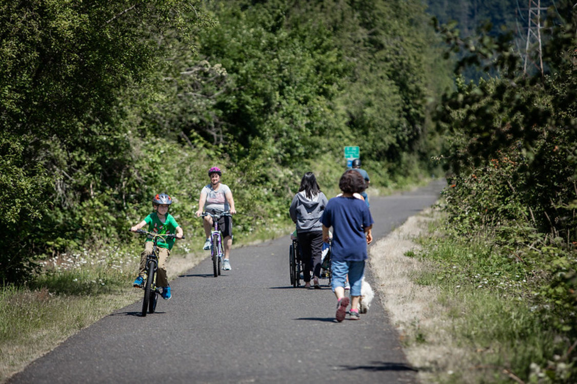 The Springwater Corridor mixed-used paved trail with cyclists, pedestrians, and people using wheelchairs sharing the paved path in greater Portland
