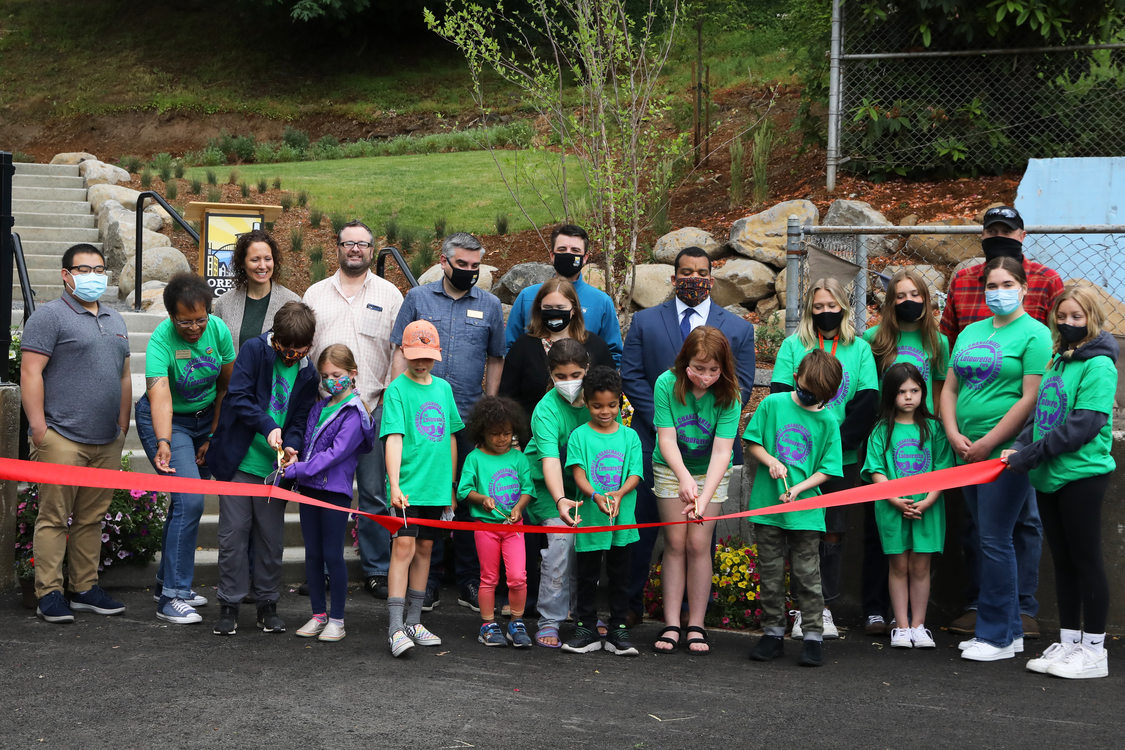 Image of children and adults cutting a ribbon to open DC Latourette Park