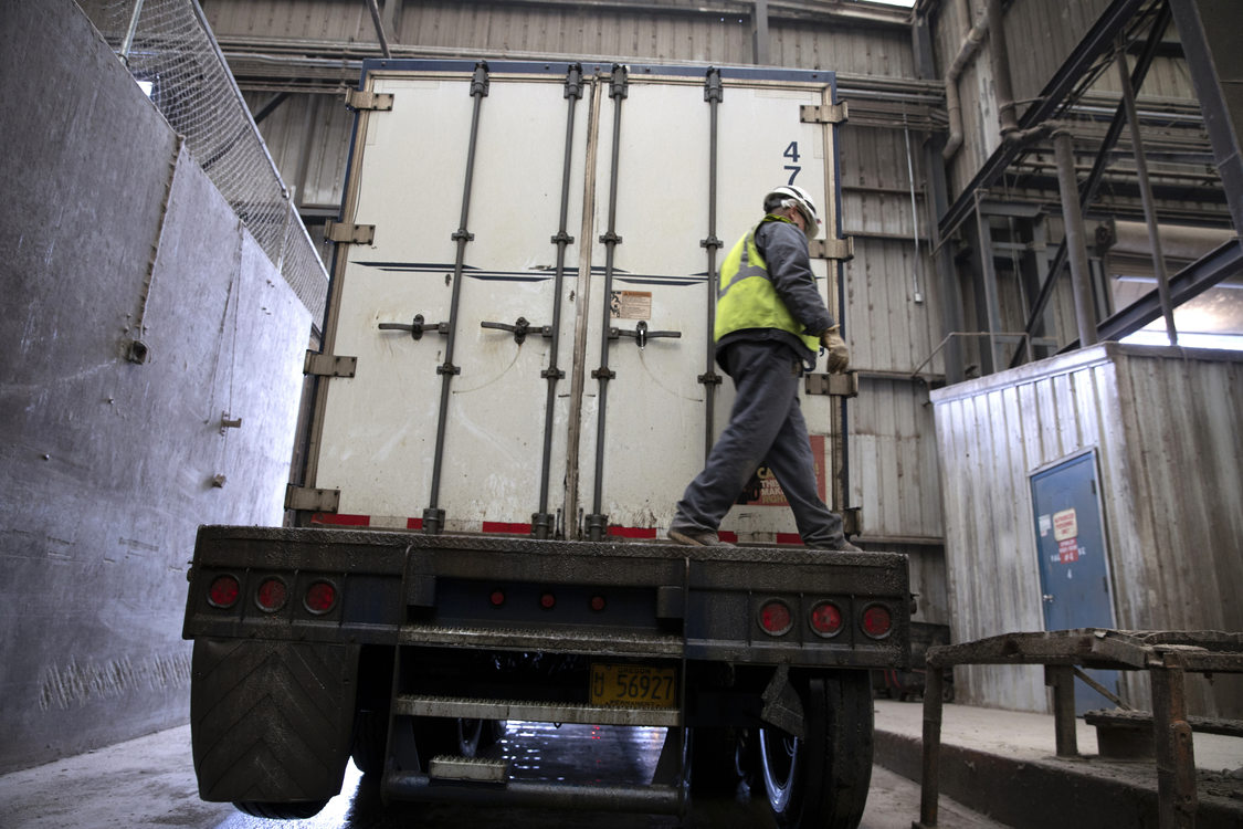 Image of Metro Central transfer station workers loading waste on a long haul vehicle