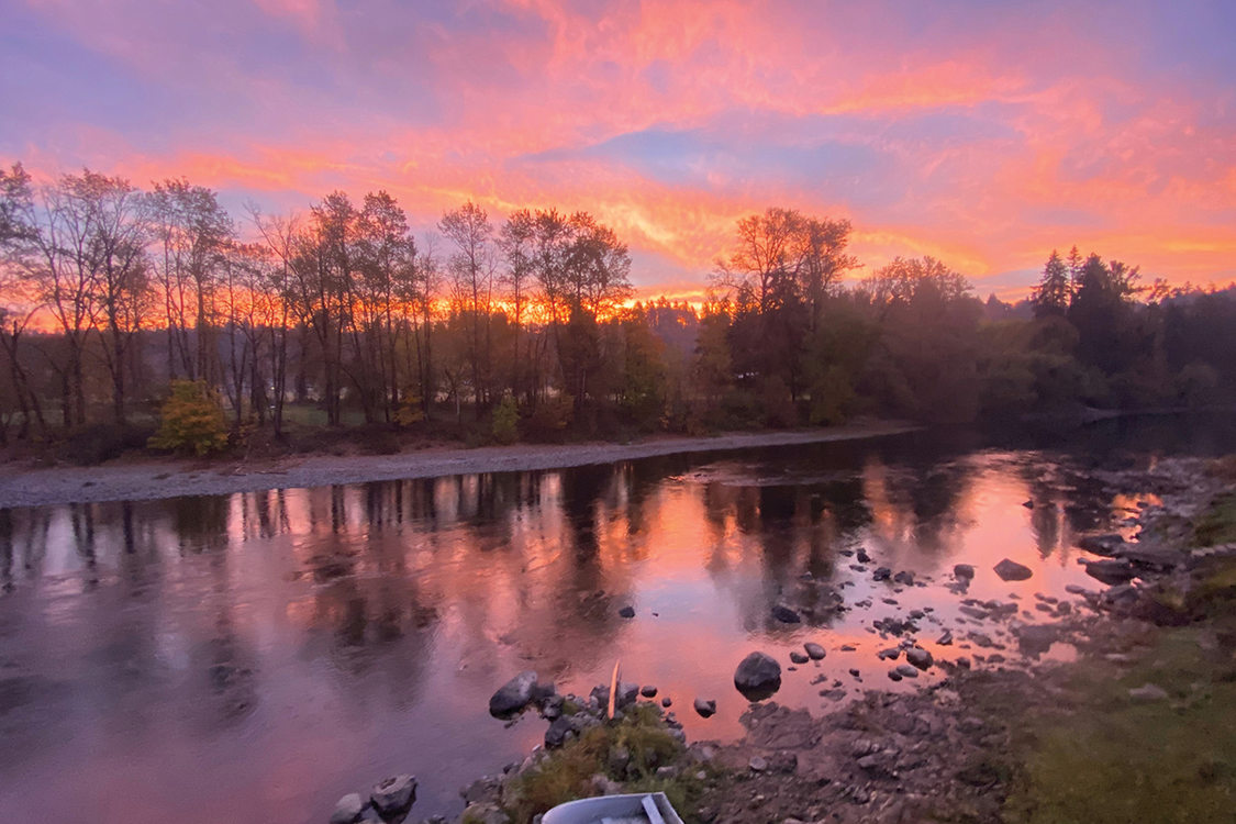 Purples, pinks and oranges fill the sky and are reflected on a river. A small boat sits on the shore.