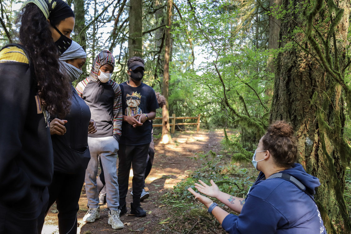 A Metro educator kneels and explains the history of Oxbow Regional Park to standing group of masked people