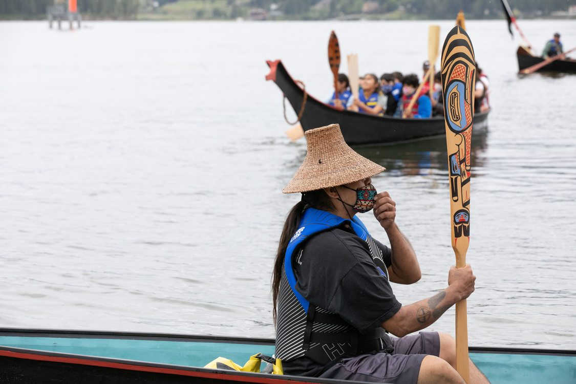 a person with a hat sits in a canoe holding a decorative oar in their hand