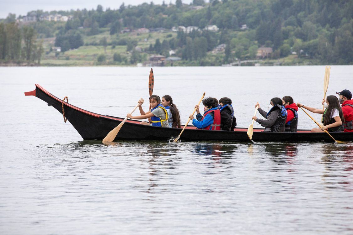 a group of young people rowing in a canoe in the Columbia River