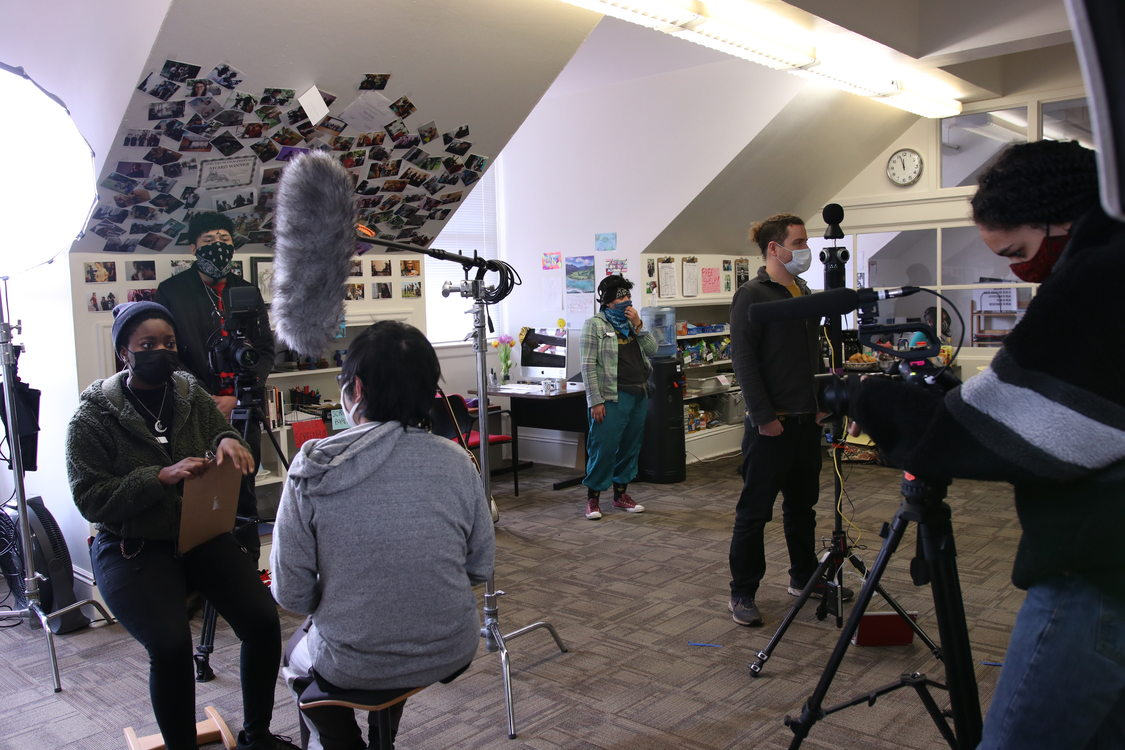 A group of young people filming on a set with camera equipment and lighting