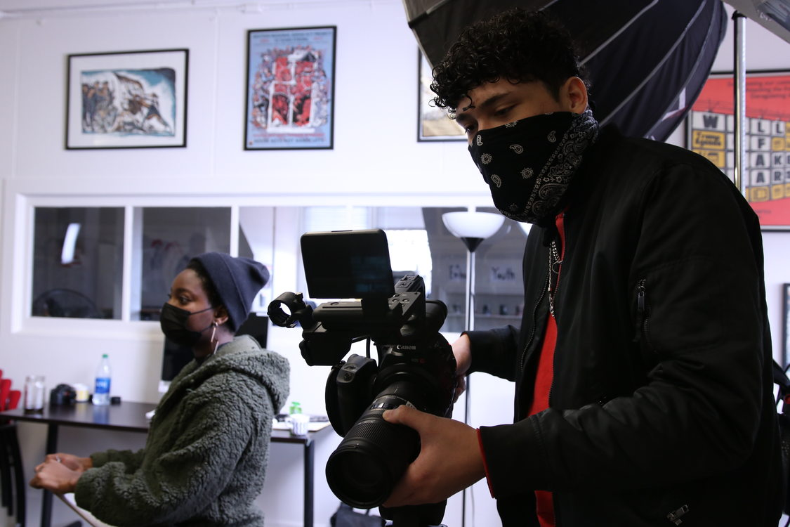 Youth holds a flmmaking camera camera to shoot a video