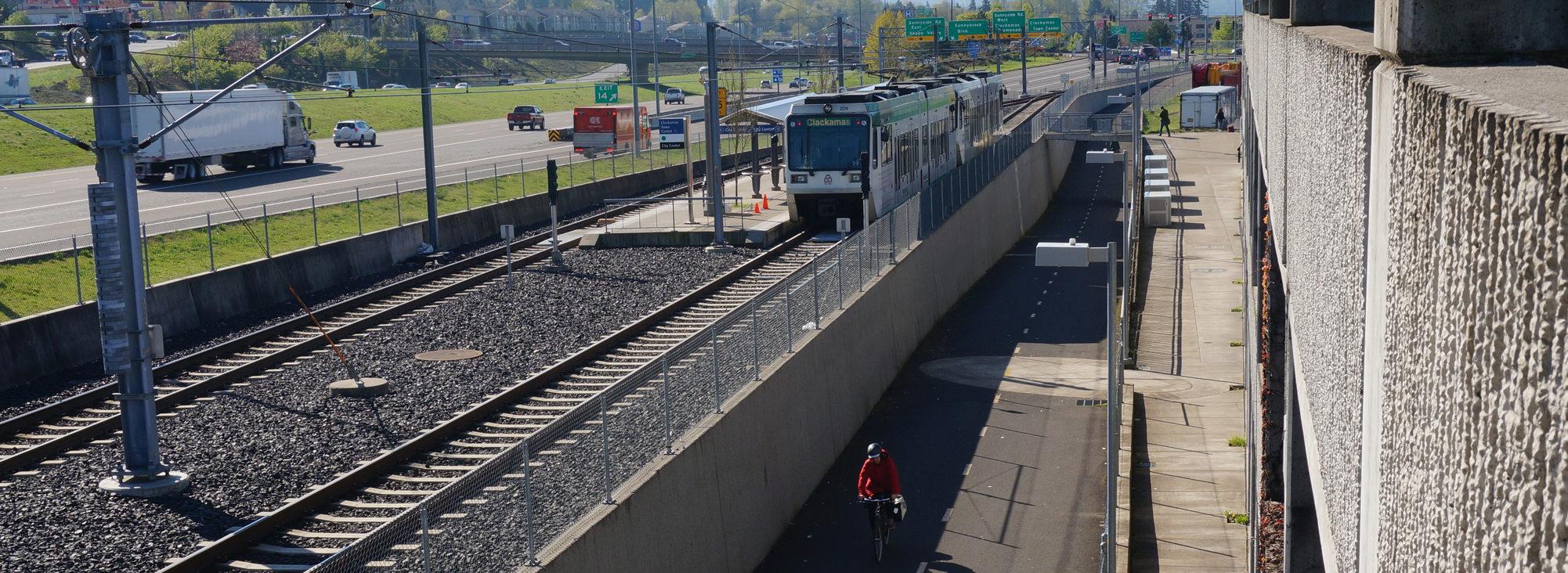 Wide shot of MAX, bike, freeway at Clackamas Town Center