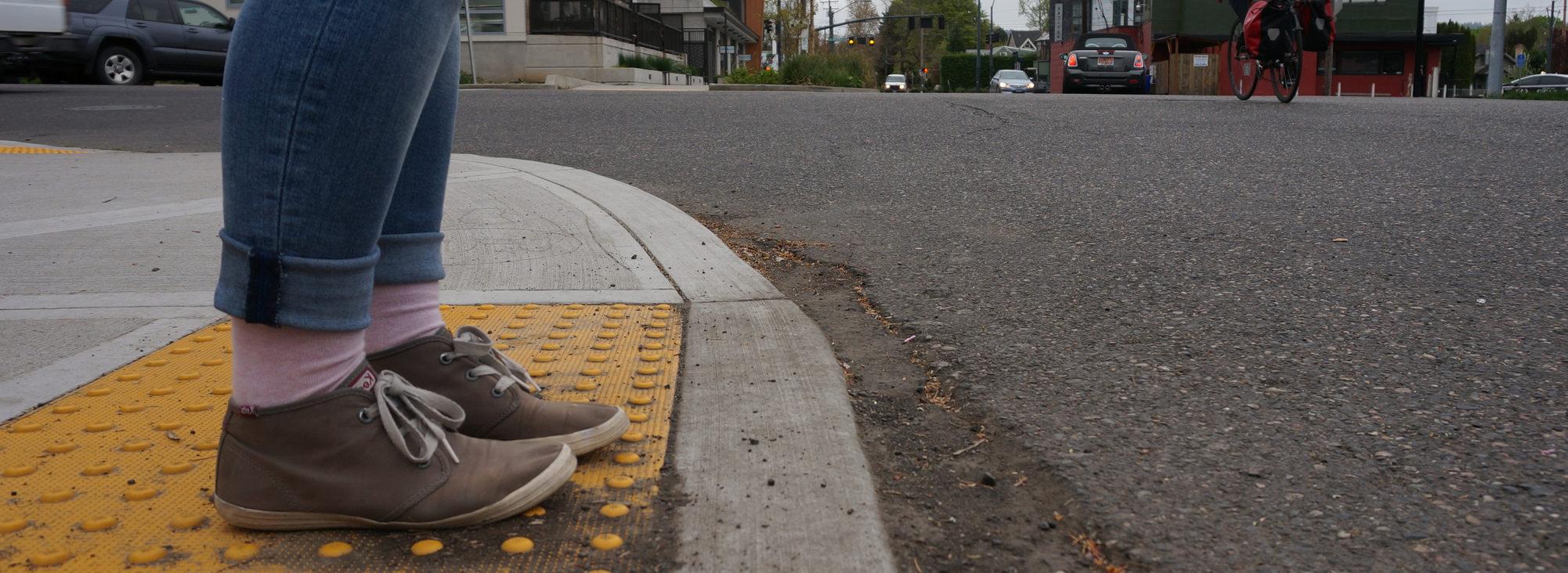 Feet waiting to cross a street