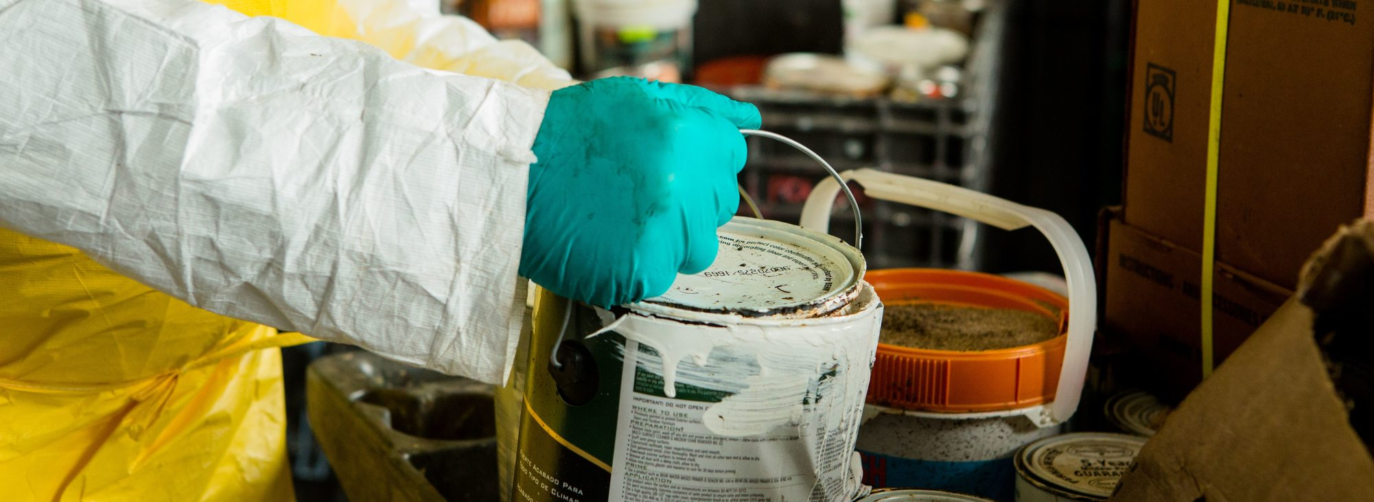 used can of paint being held by a hazardous waste technician