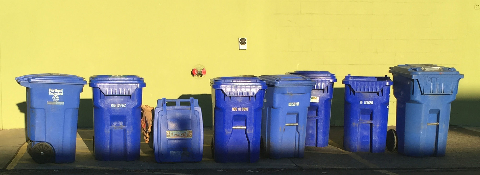 blue recycling bins against a yellow wall