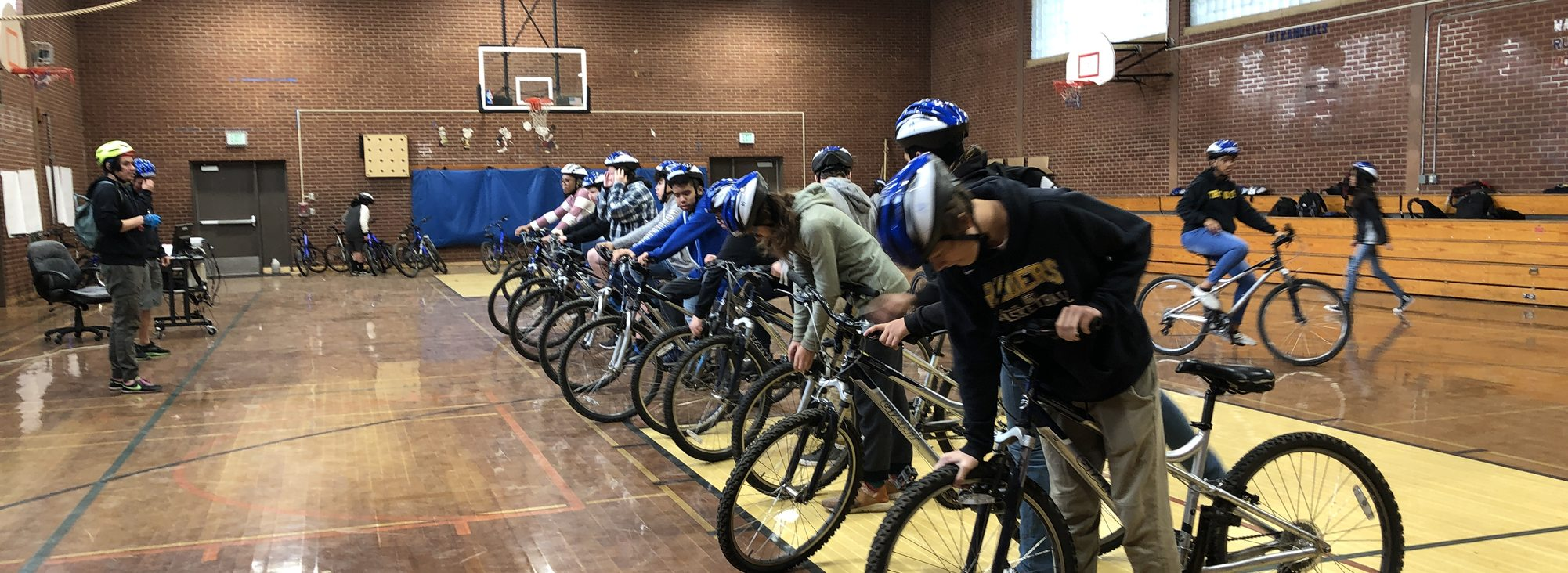 at a school gym, middle school students check the tire pressure on their bikes as they form a line side to side in front of their instructors