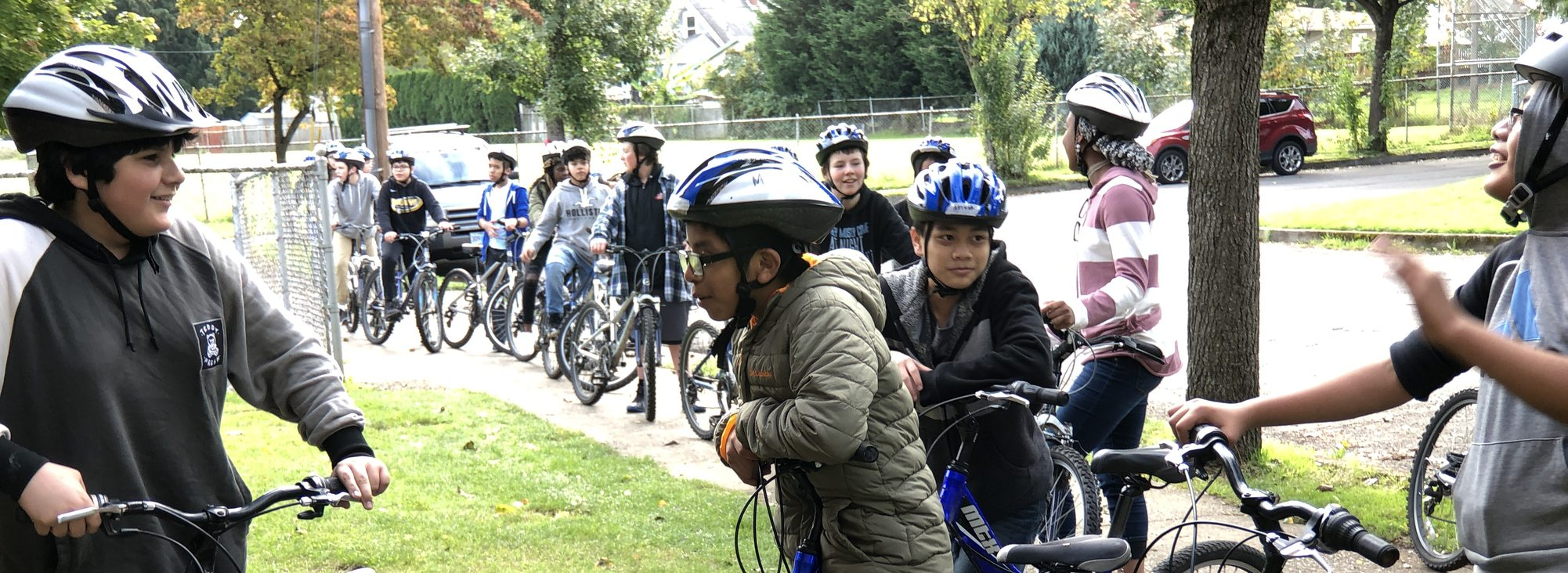middle school students mounted on their bikes get in line on a sidewalk to return to gym class
