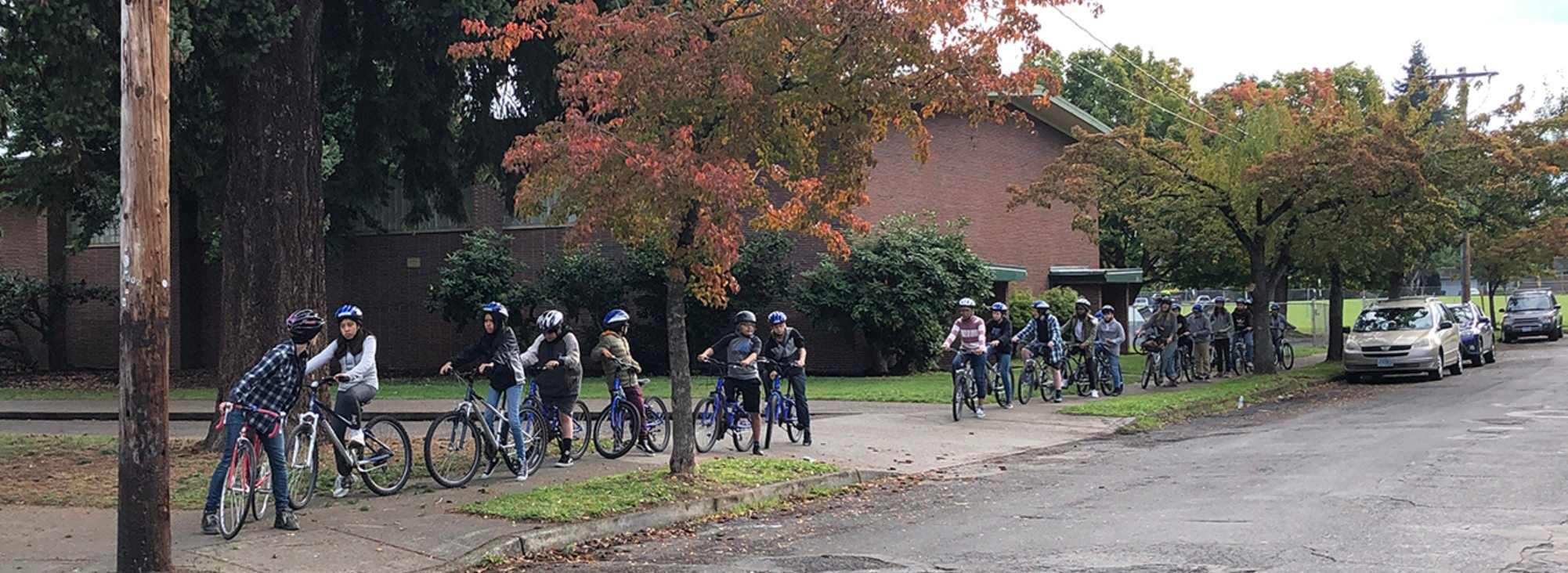 Middle school students, mounted on bikes, form a line on a sidewalk outside their school