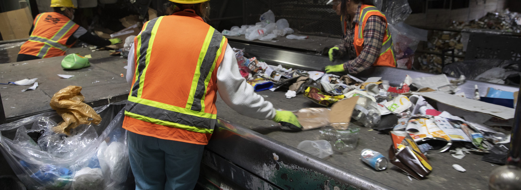 workers at a materials sorting facility pull out plastic bags and other non-recyclable items