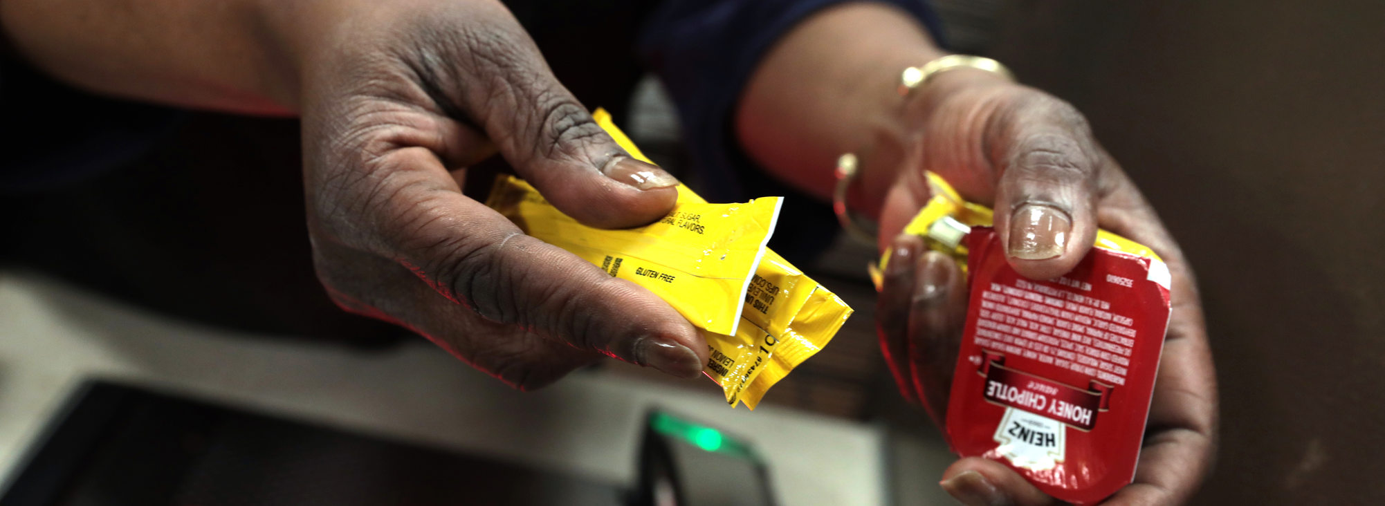a deli worker hands some condiment packages to a customer who asked  for them
