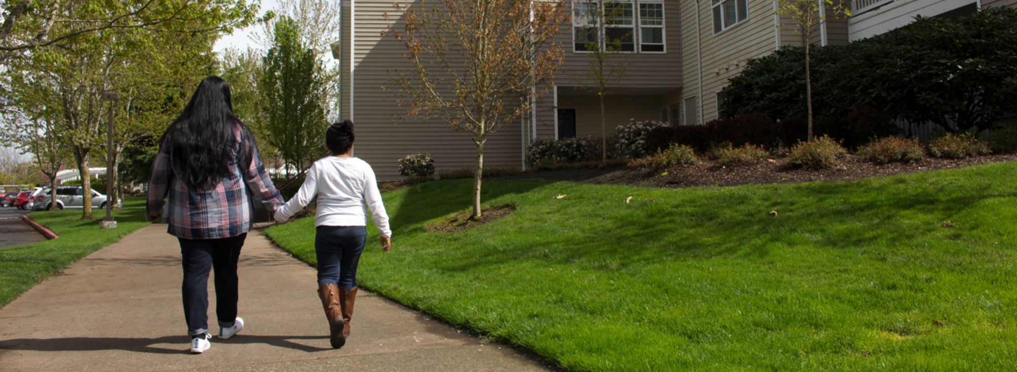 an adult and a child walk hand-in-hand on a sidewalk in front of an apartment complex
