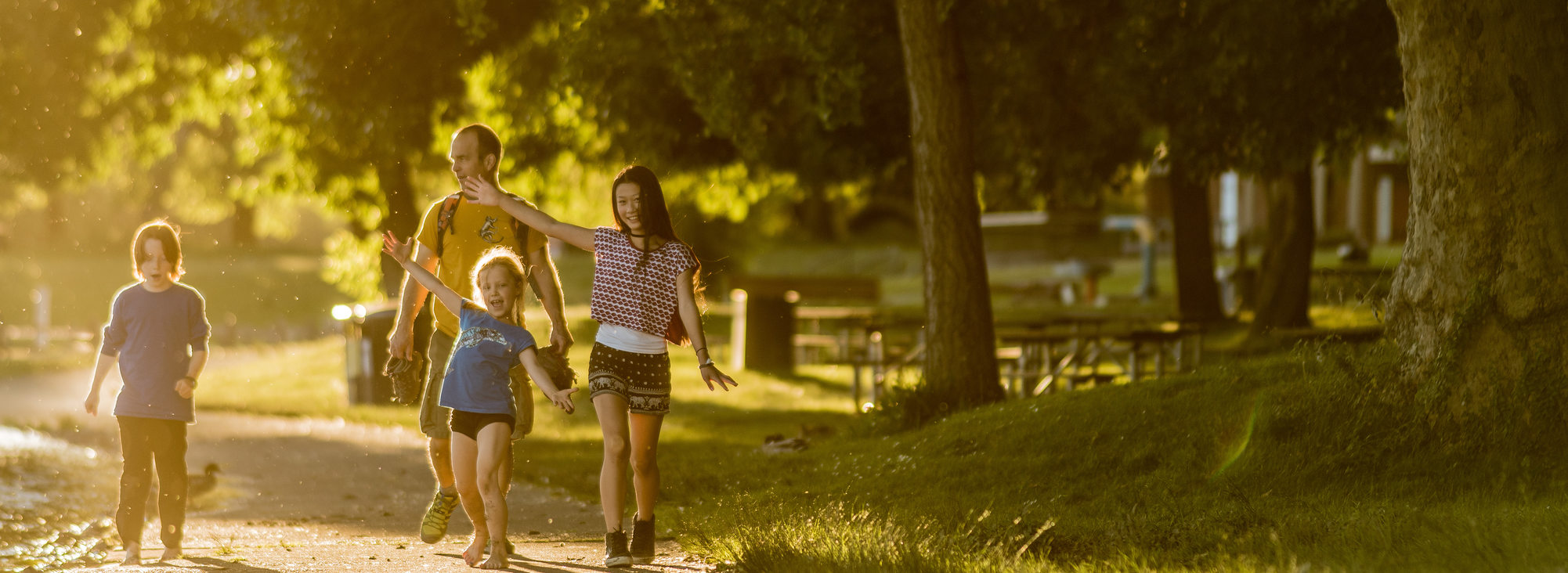 A family of four, one adult and three kids, walks along the path at Blue Lake Park