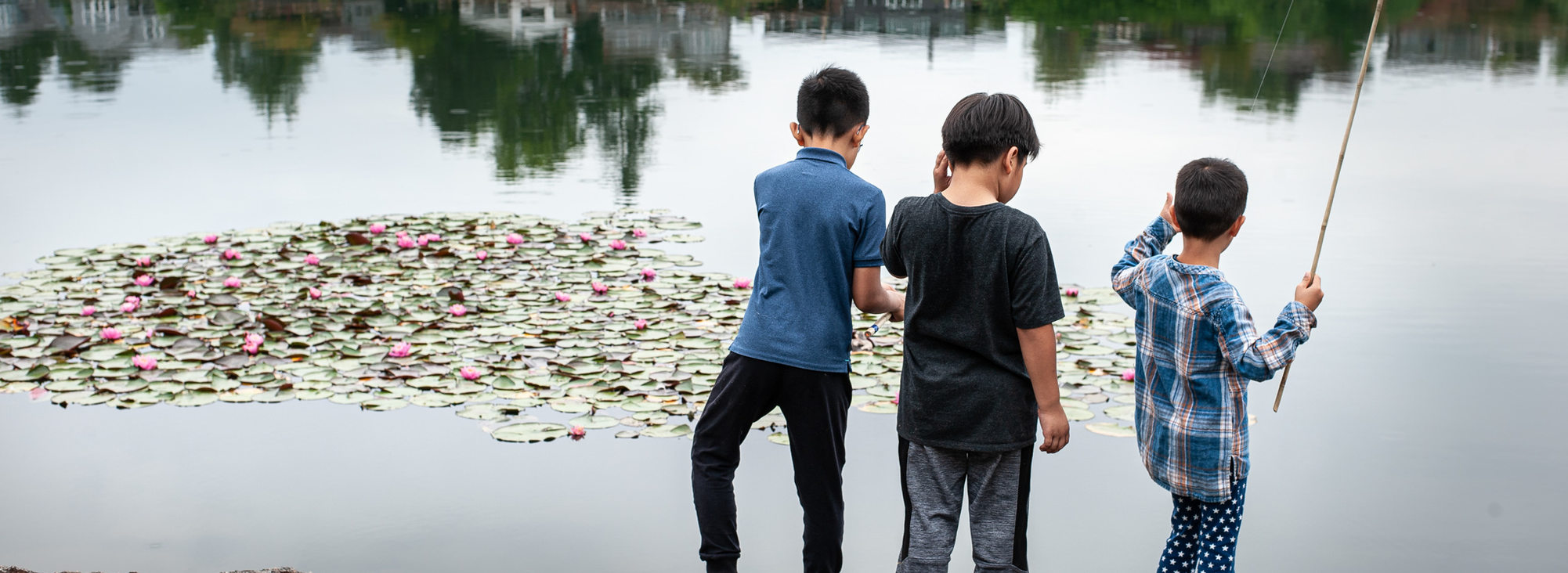 Three kids fishing from the shoreline at Blue Lake Park