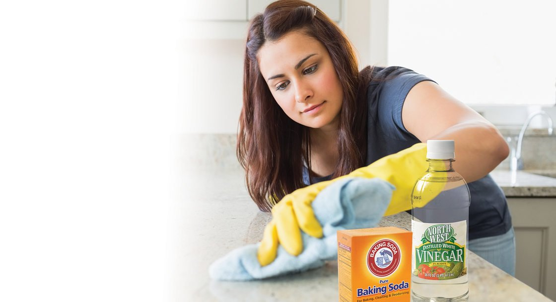photo of woman cleaning with baking soda and vinegar