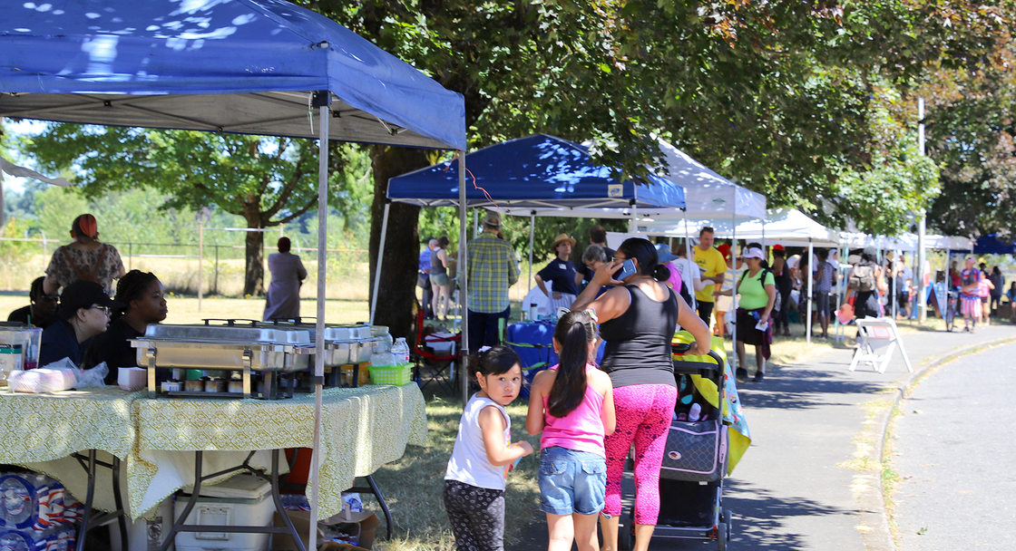Families walk past park vendors on a tree-lined street.