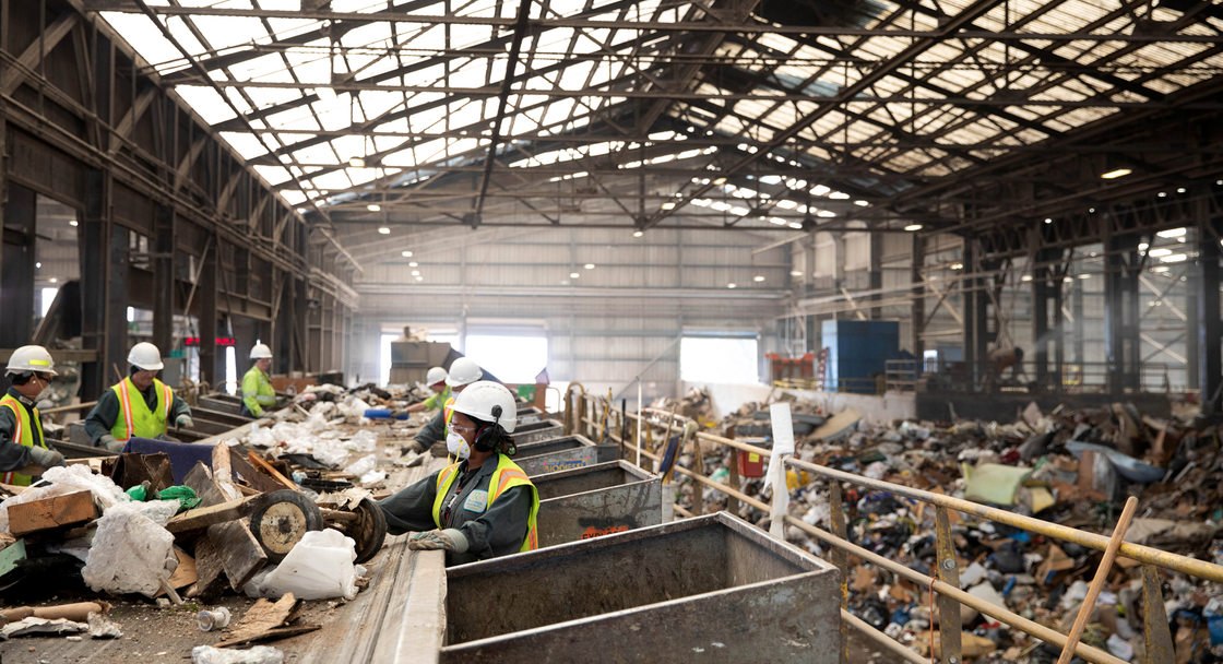 workers near a conveyor belt sort recyclable material from garbage