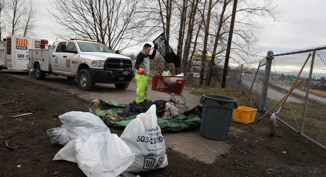A man goes through dumped garbage on a bluff overlooking a highway