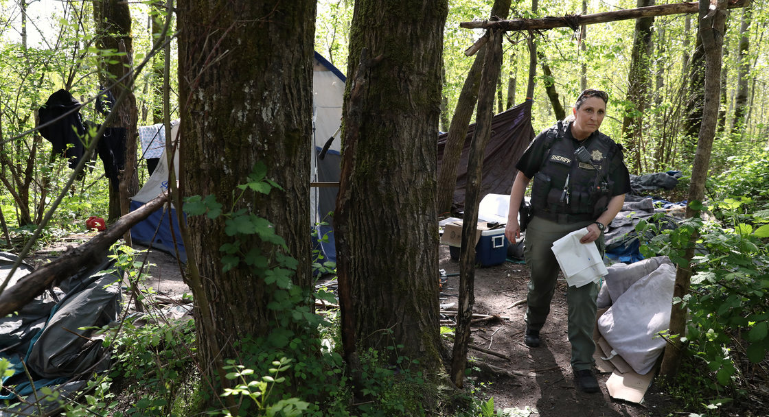 a sheriff deputy, carrying a handful of white garbage bags, visits a campsite in the woods.