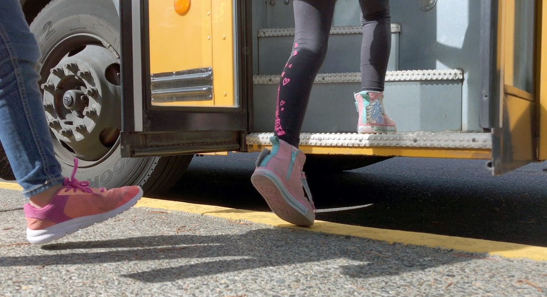the feet of school children boarding a bus