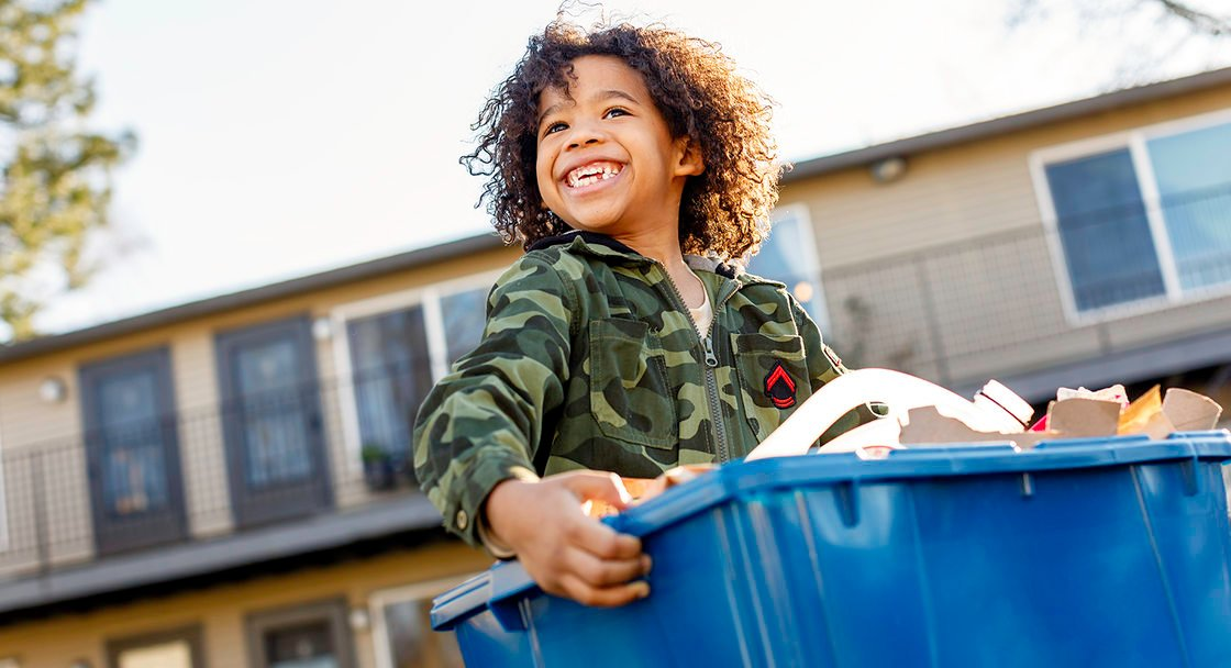 smiling child carrying a full recycling bin