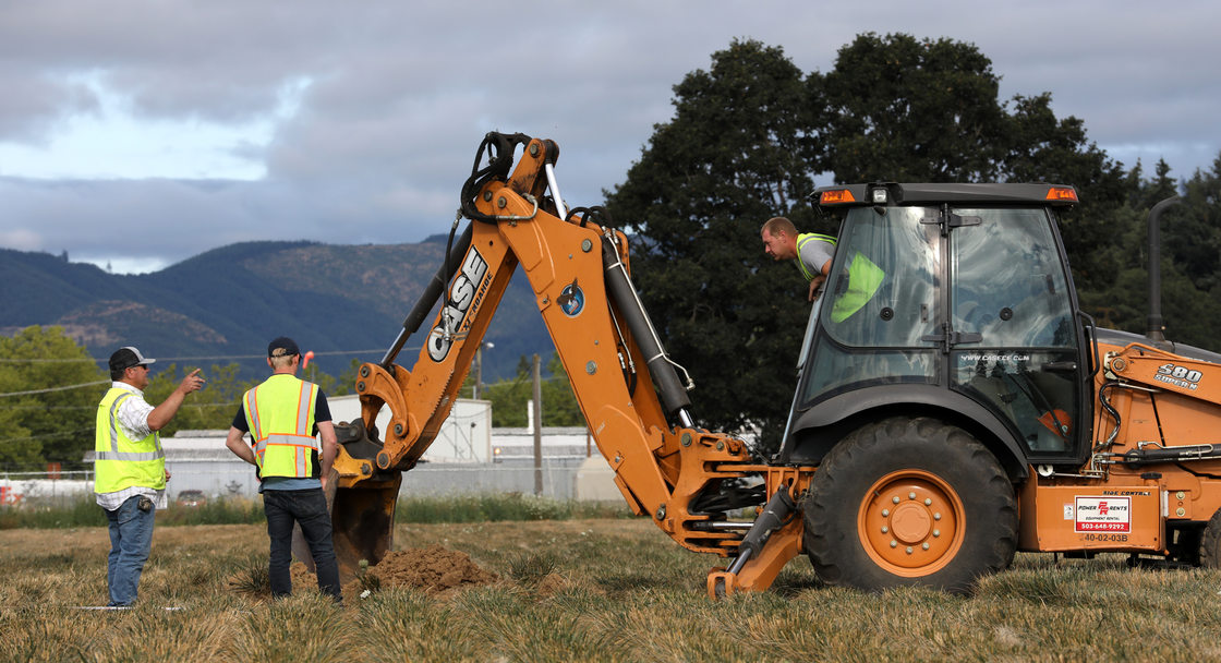 A tractor operator leans out of his tractor cab to converse with two co-workrs at a test site in rural  Washington County.