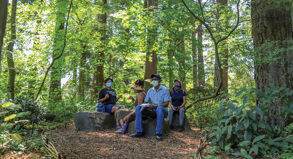 Four people of color sit on boulders in a sun-dappled clearing in a forest.