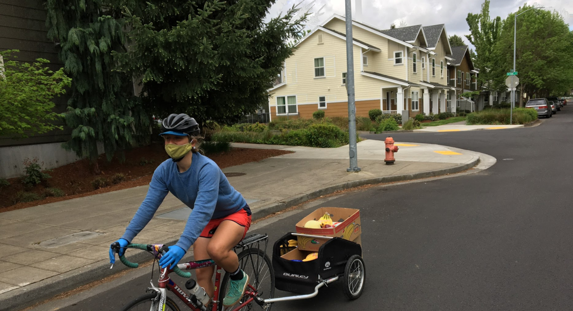 A person biking while hauling a trailer with boxes of food for delivery