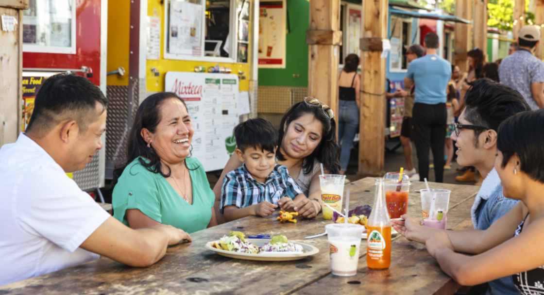 Family eats at a table in front of food trucks