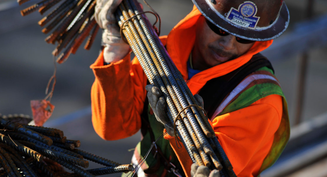 a construction worker carries a bundle of metal rebar at a construction site
