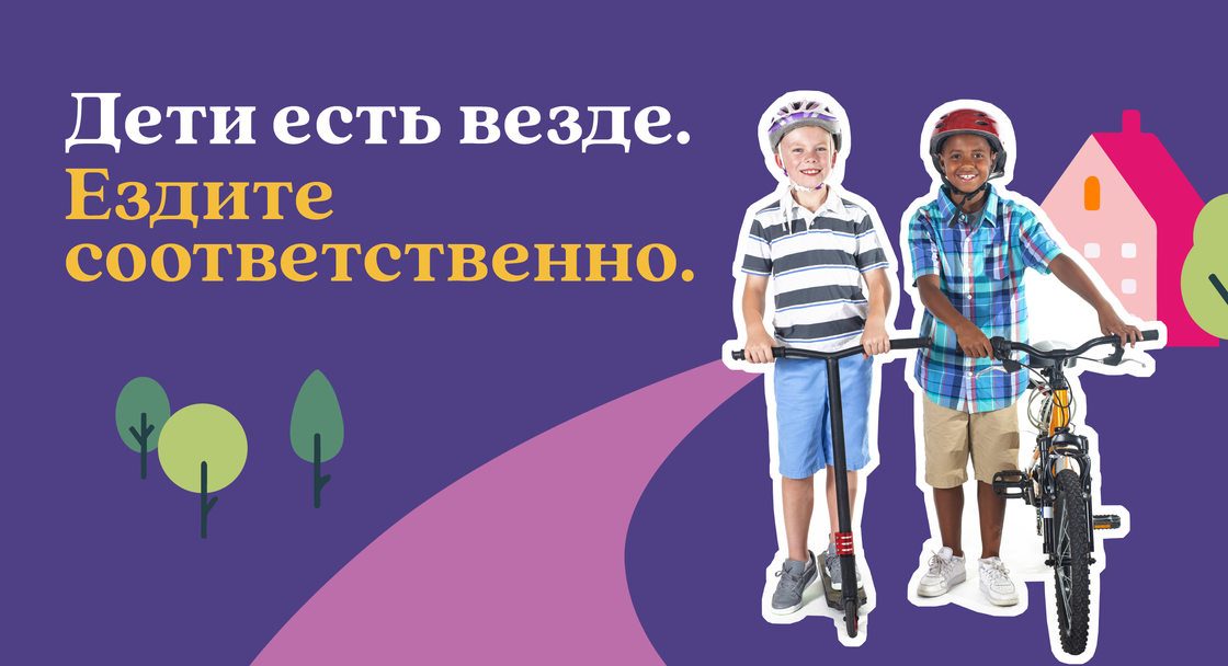 "Safety campaign poster in Russian for Safe Routes to School showing one child on a bike with another child on a scooter. The text on the image says ""Kids are everywhere. Drive like it"" translated into Russian"