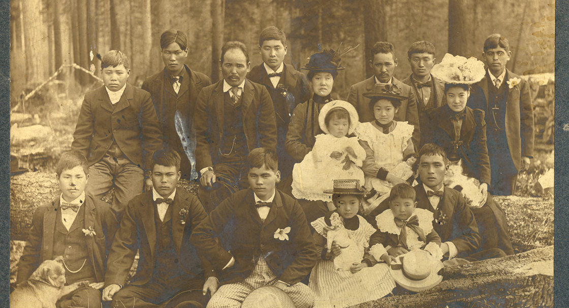 A sepia-toned photo of group of about 20 Japanese people in suits and dresses posing for a photo in a forest.