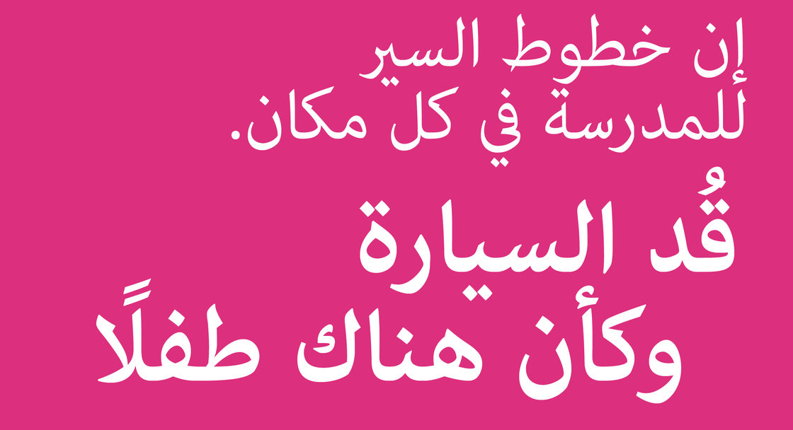 """Safety campaign poster with text saying """"School routes are everywhere. Drive like it"""" in Arabic."""