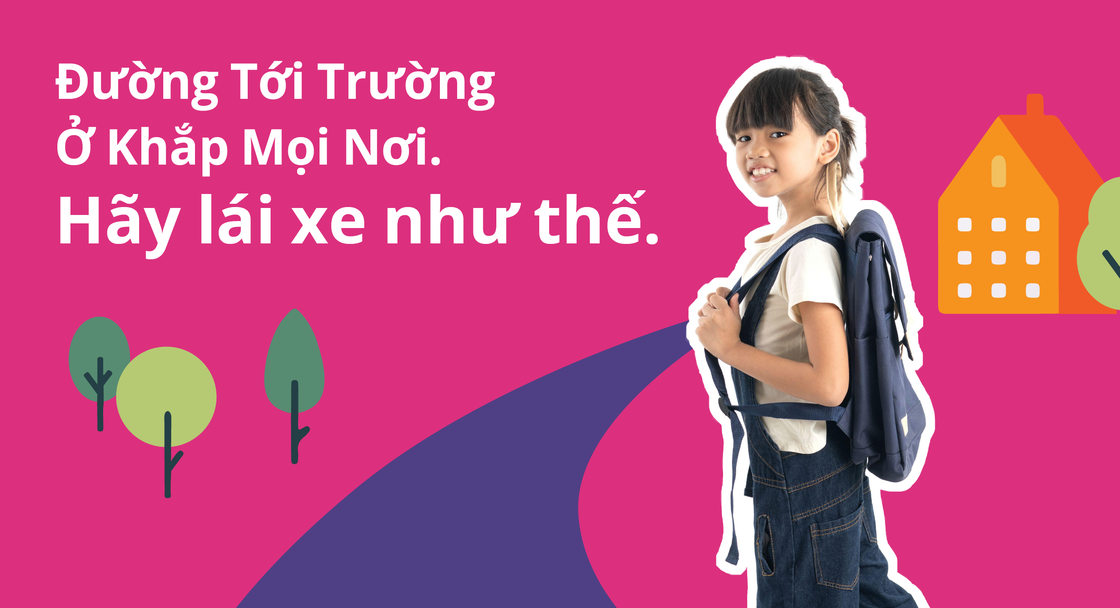 """A child wearing a backpack appears in a safety campaign poster with a message in Vietnamese reading """"School routes are everywhere. Drive like it."""""""