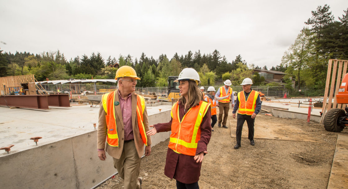 Don Moore and Heidi Rahn, wearing hard hats and safety vests, walk through the elephant prairie construction site at the Oregon Zoo. More people wearing hard hats and safety vests are seen in the background.