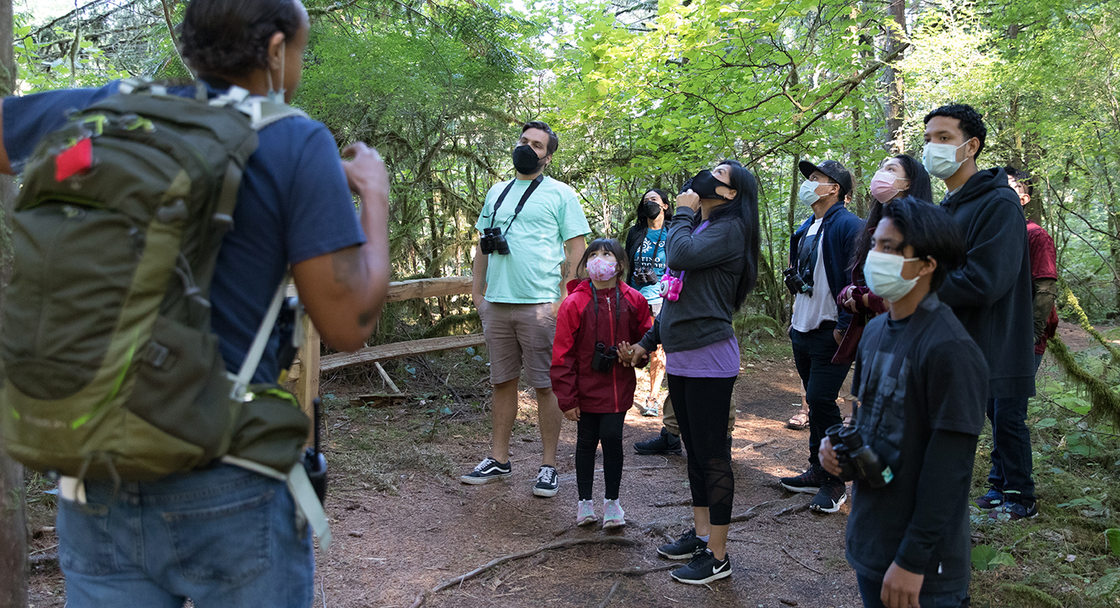 A group of hikers wearing masks listen to a nature educator wearing a large backpack.
