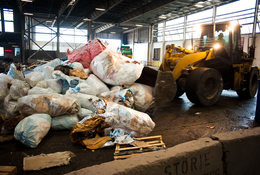photo of a backhoe moving garbage at a transfer station