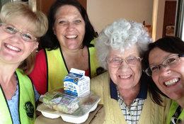 food recipient poses with volunteers