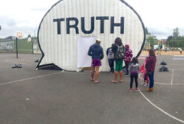 "A school's playground with an art exhibit, specifically a tent in the shape of a comment bubble with the word ""truth"" across it"