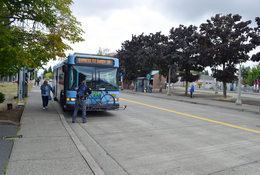 man loading bike onto a Sandy Area Metro bus; woman about to board bus