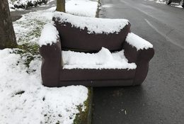 couch on curb with an inch of snow on it