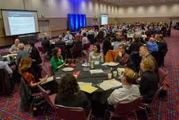 In a ballroom at the Oregon Convention Center, people discuss the future of transportation projects