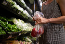 a woman uses plastic bag for her produce in the supermarket