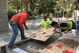 Workers imprint animal tracks in fresh concrete at Oxbow Regional Park welcome center.